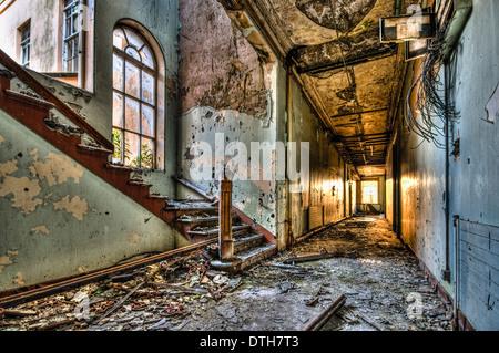 Corridor in a derelict building, with sunlight shining through far window - Stock Photo