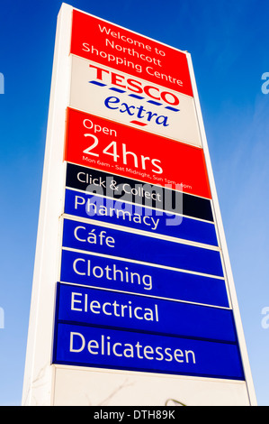 Tesco Extra 24 hours sign with pharmacy, cafe (spelled incorrectly), clothing, electrical and delicatessen - Stock Photo