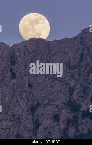 Real full moon rising over Serra d'Alfàbia mountain at dusk. Tramuntana hills, Sóller area, Majorca, Balearic islands, Spain