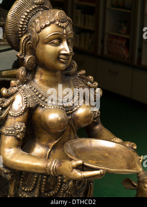 India, Kerala, Fort Cochin, Mattancherry, cast brass figure of bare breasted woman holding tray in antique shop - Stock Photo