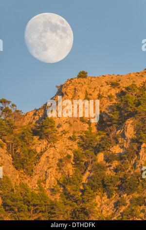 Real full moon rising over Puig des Teix mountain at sunset. Tramuntana mountains, Deià, Majorca, Balearic islands, Spain