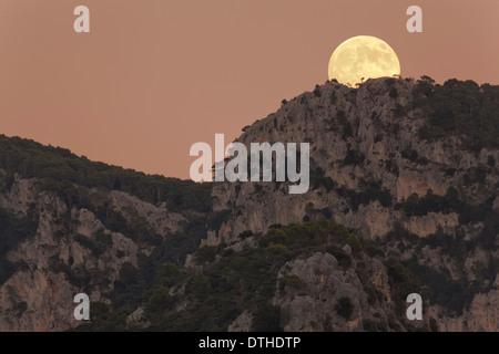 Real full moon rising over Penyal d'Honor mountain at dusk. Tramuntana hills, Bunyola area, Majorca, Balearic islands, Spain