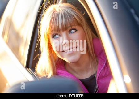 Smiling beautiful girl looks out of a car window - Stock Photo