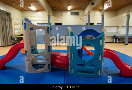 Slides and other toys in a playroom in a children's daycare - Stock Photo
