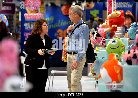 New York, NY, USA. 18th Feb, 2014. An exhibitor (L) talks with a visitor at the 111th American International Toy - Stock Photo