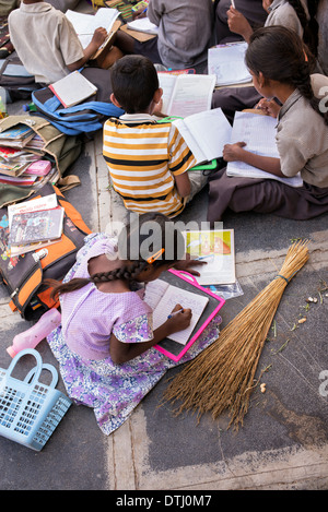 Indian children doing school work outside a rural Indian village house. Andhra Pradesh, India - Stock Photo
