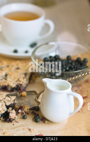 White jug of milk on table with breakfast with homemade blueberry pie and bowl of fresh blueberries - Stock Photo
