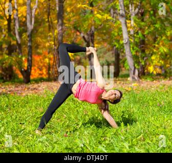 Woman exercises in the autumn forest yoga Ardha Chandra chapasana pose - Stock Photo