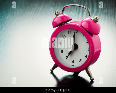 pink Alarm clock on bedside table - Stock Photo