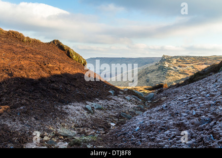 Frost melting in Winter sunshine in a gulley a on peat moor at Fairbrook Naze on Kinder Scout, with Seal Edge in - Stock Photo