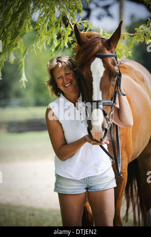 A woman standing next to a bayhorse with a halter rein  England - Stock Photo