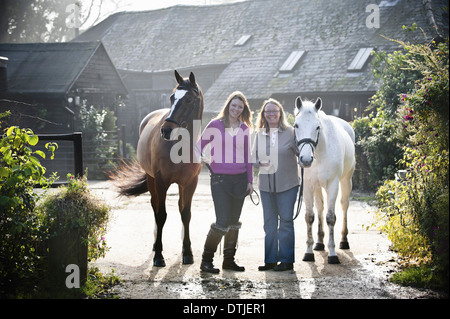 Two women standing outside a stable with two horses England - Stock Photo