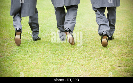 Groom and two best man in black shoes grey trousers and morning coats walking along a lawn Back view  England - Stock Photo