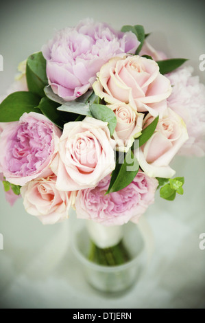 A bridal bouquet of pastel coloured pink roses and pale lavender peonies with small green leaves  England
