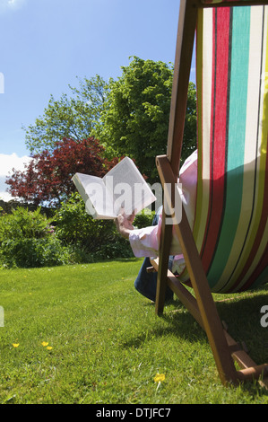 A person sitting in a deckchair reading Gloucestershire England - Stock Photo