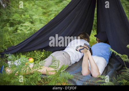 Two boys camping in the New Forest lying under a canvas shelter Hampshire England - Stock Photo