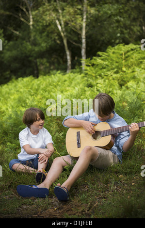 Two boys camping in New Forest Sitting on the grass one playing a guitar  Hampshire England - Stock Photo