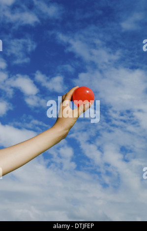 A person's outstretched hand holding a red ball Gloucestershire England - Stock Photo