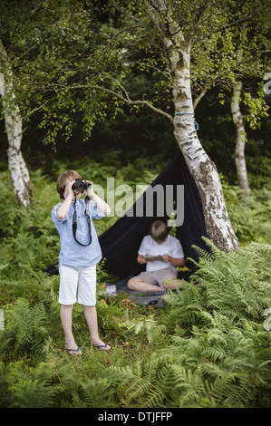 Two boys camping in New Forest One sitting under a black canvas shelter  One boy looking through binoculars Hampshire - Stock Photo