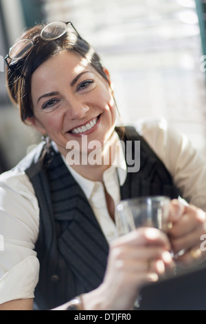 A woman holding a glass and smiling at the camera A working lunch  New Hope Pennsylvania USA - Stock Photo