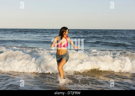 A beautiful young women at the water's edge on the beach in Atlantic City New Jersey USA - Stock Photo