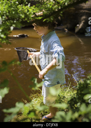 A young boy holding a fishing net by a shallow river Camping in the New Forest Hampshire England - Stock Photo