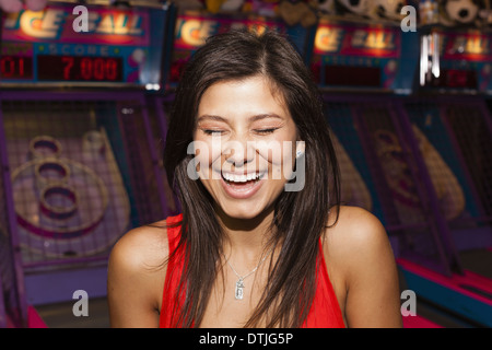 A beautiful young woman on the boardwalk in Atlantic City in front of a row of slot machines  New Jersey USA - Stock Photo