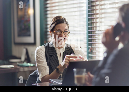 A woman and man in an office at their desks working over lunch New Hope Pennsylvania USA - Stock Photo