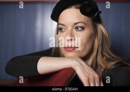 A woman in a theatre wearing an evening hat and black top Resting her chin on her hand looking away in an elegant - Stock Photo