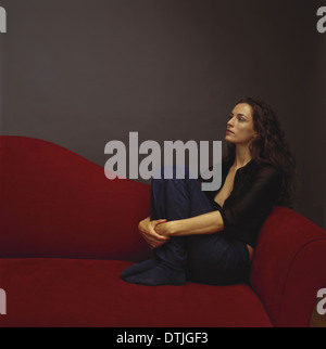 A woman dressed in black seated on a red couch Cape Town South Africa - Stock Photo