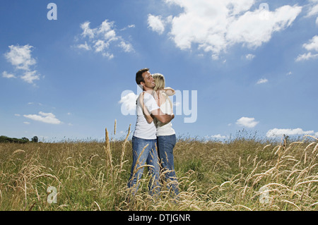 A couple standing in a field of wheat hugging England - Stock Photo