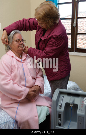 Assistant helping out elderly patient put on nasal cannula to do oxygen therapy with air machine at home - Stock Photo