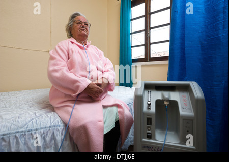 Elderly patient doing oxygen therapy with air machine at home - Stock Photo
