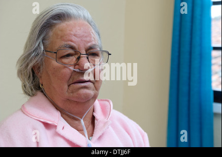 Elderly patient doing oxygen therapy with nasal cannula - Stock Photo