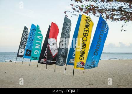 Flags with sports brands in the surf on the beach during a windy day Sanur Thailand