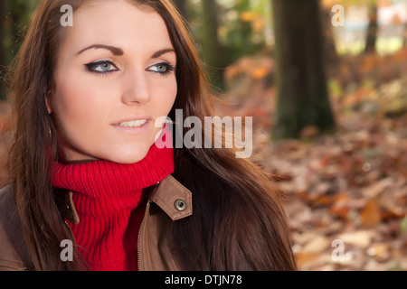 Happy brunette is having a nice time in the park while it's autumn - Stock Photo