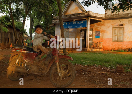 Child up in an old bike near  Boeng Yeak Lom Lake. Ratanakiri. Ratanakiri is a province in northeastern Cambodia - Stock Photo
