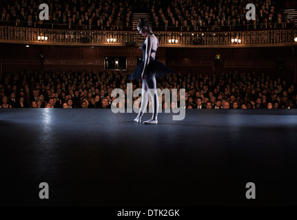 Ballet dancer performing on stage in theater - Stock Photo