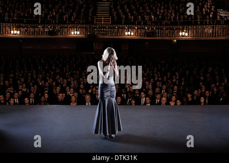 Performer with head in hands on stage in theater - Stock Photo