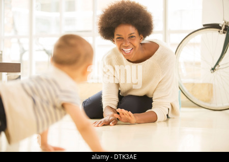 Mother and baby son playing on living room floor - Stock Photo