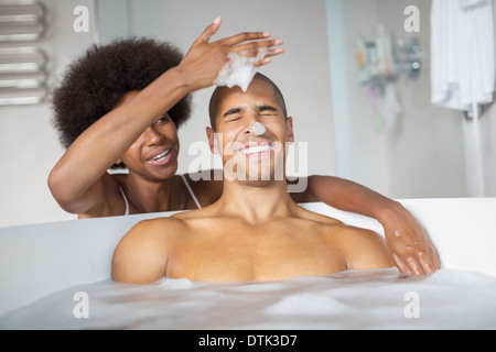 Woman playing with boyfriend in bubble bath - Stock Photo
