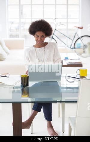 Woman using laptop at desk - Stock Photo