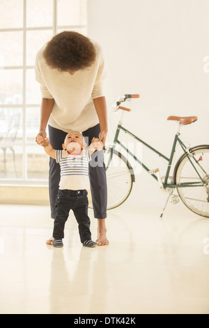 Mother helping baby boy walk in living room - Stock Photo