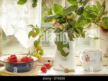 Apples and fresh strawberries on a old windowsill - Stock Photo