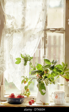 Bouquet from branches of apple and plum trees and a bowl of strawberries on an old window sill - Stock Photo