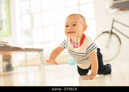 Baby boy crawling on living room floor - Stock Photo