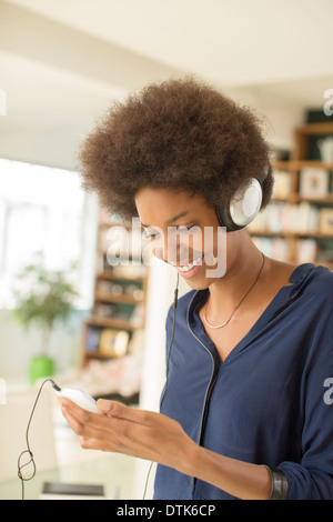 Woman listening to headphones in living room - Stock Photo