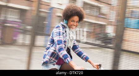 Woman riding bicycle on city street - Stock Photo