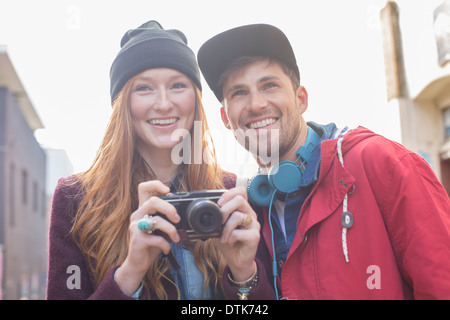Couple taking photographs with camera in city - Stock Photo