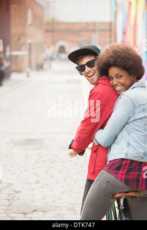 Couple riding bicycle together on city street - Stock Photo